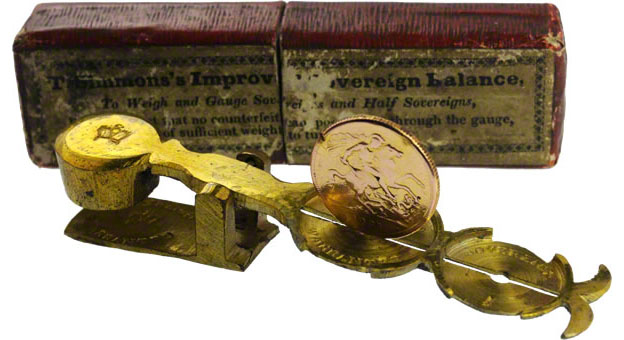 A sovereign balance with a fake sovereign that's too wide to pass through the slot.